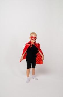 Mały chłopiec w stroju superbohatera stoi na białym tle