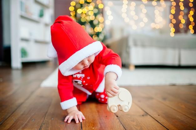 Mały chłopiec w stroju świętego mikołaja bawi się na podłodze drewnianym samochodzikiem na tle świateł noworocznych