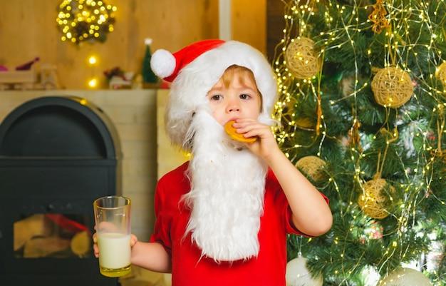 Mały chłopiec w stroju świętego mikołaja je ciastko z mlekiem