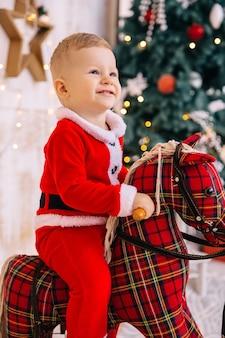 Mały chłopiec w stroju świętego mikołaja patrzy w górę i uśmiecha się. dziecko siedzi na koniu na biegunach.
