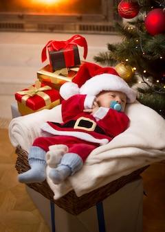 Mały chłopiec w stroju świętego mikołaja śpi w noc bożego narodzenia w salonie