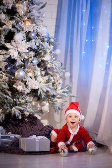 Mały chłopiec w stroju świętego mikołaja w bożonarodzeniowym pokoju w pobliżu choinki na tle świateł.