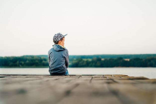 Mały chłopiec w stylowej czapce i kurtce wygląda na odległość na moście nad jeziorem.