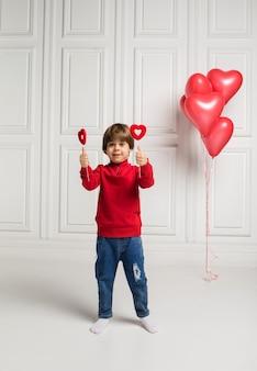 Mały chłopiec w swetrze i dżinsach trzyma serca na kiju na białym z balonami