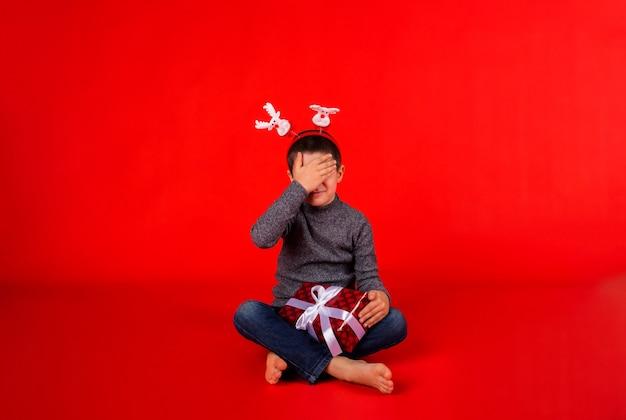 Mały chłopiec w swetrze i świątecznej opasce z reniferem