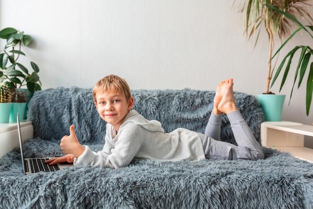 Mały chłopiec w szkole o połączenie wideo, lekcje online na laptopie e-learning, nauka na odległość, koncepcja komunikacji na odległość