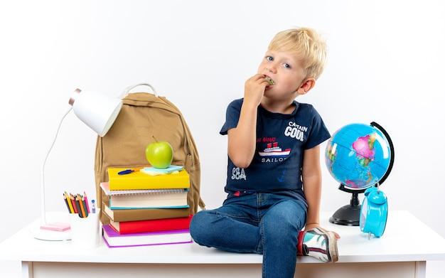 Mały chłopiec w szkole siedzący na stole z szkolnymi narzędziami jedzący kawałek jabłek