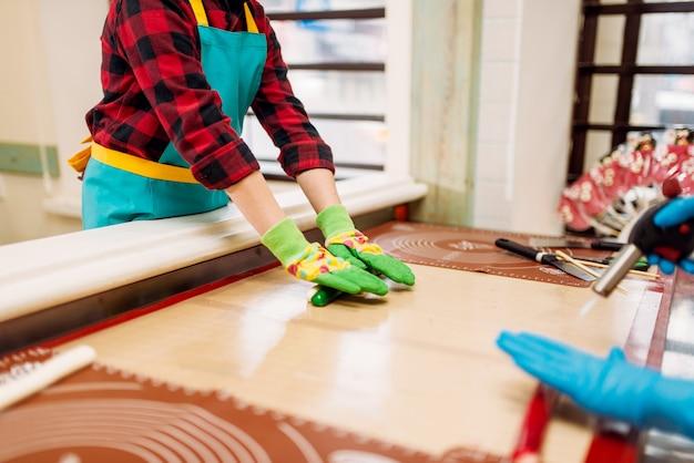Mały chłopiec w warsztacie w cukierni uczy się robić karmel. wakacyjna zabawa w sklepie ze słodyczami. proces przygotowania lollipopa