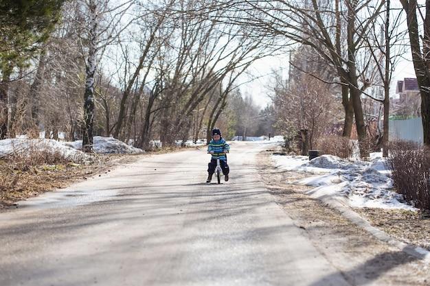 Mały chłopiec w wieku 2 lat uczy się jeździć na rowerze biegowym na drodze we wsi