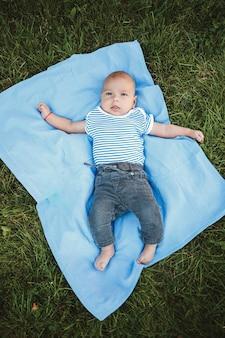 Mały chłopiec w wieku 3 miesięcy leży na plecach na niebieskiej narzucie w parku wokół zielonej trawy i drzew. dziecięce emocje radości