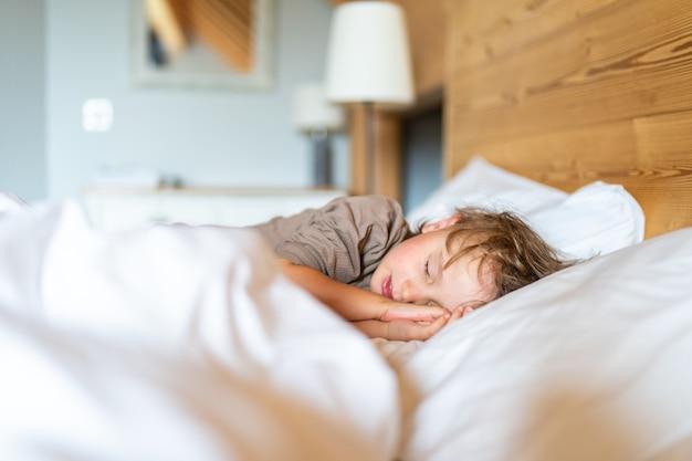 Mały chłopiec w wieku przedszkolnym w piżamie śpi w łóżku w domu. dziecko nie chce obudzić się rano.