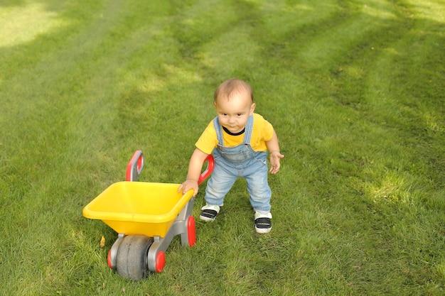 Mały chłopiec w żółtej koszulce i dżinsach bawi się na trawniku w parku żółtym wózkiem