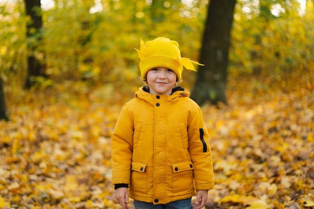 Mały chłopiec w żółtym kapeluszu i kurtce spaceruje po jesiennym lesie dzieci są aktywne na łonie natury