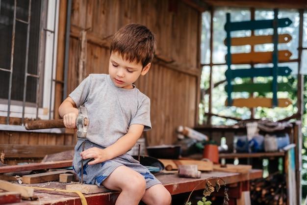 Mały chłopiec wbija gwoździe młotkiem w drewnianą deskę w warsztacie stolarskim