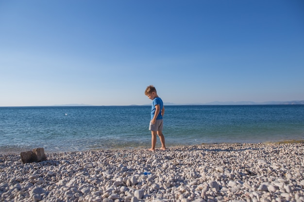 Mały chłopiec wchodzi do morza, widok z tyłu. letnia koncepcja wakacji i niewinności. beztroskie dzieciństwo.