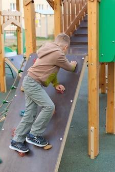 Mały chłopiec wspina się na otwartym placu zabaw. dzieci bawią się w słonecznym letnim parku. centrum rozrywki i rozrywki na dziedzińcu przedszkolnym lub szkolnym. dziecko na zewnątrz.