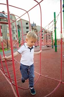 Mały chłopiec wspina się po linach na placu zabaw na tle domów w lecie