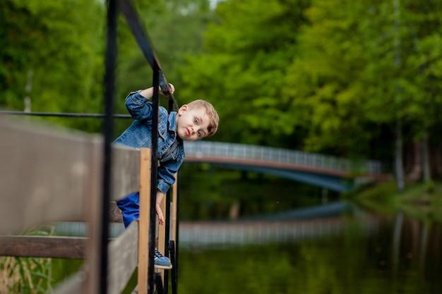 Mały chłopiec wspina się po poręczy mostu w parku.