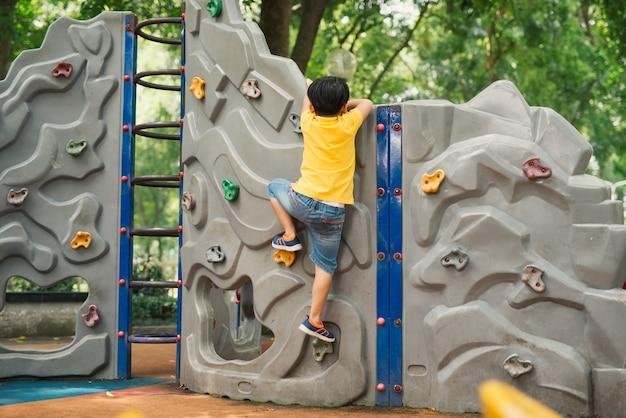 Mały chłopiec wspinający się po ścianie skał na placu zabaw
