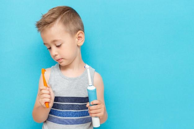 Mały chłopiec wybiera szczoteczkę elektryczną i tradycyjną