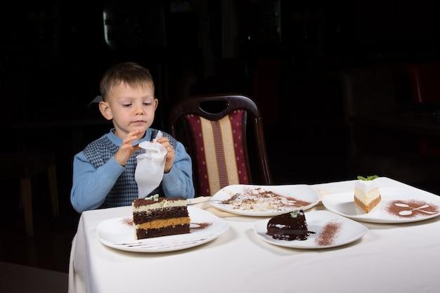 Mały chłopiec wykańcza kawałek ciasta przy stole ułożonym z asortymentem ciast podawanych na osobnych talerzach na ciemnym tle