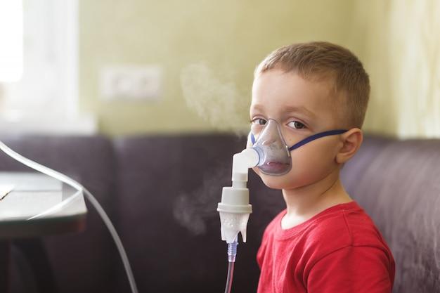 Mały chłopiec wykonuje terapeutyczne inhalacje