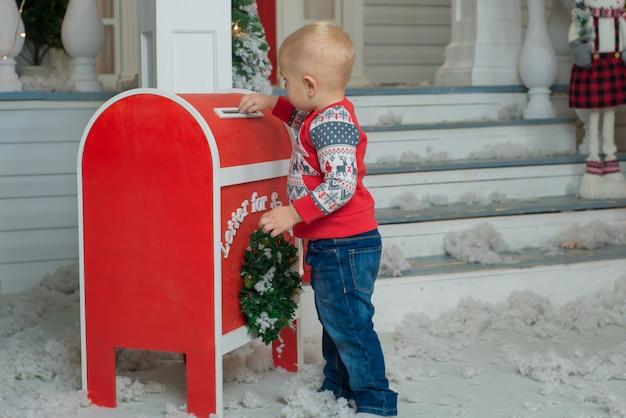 Mały chłopiec wysyłający list do świętego mikołaja
