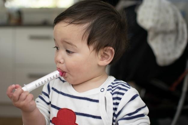 Mały chłopiec wysysa lek ze strzykawki w domu, podczas gdy zachorujesz