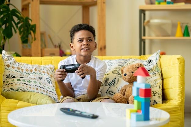 Mały chłopiec z afryki lub rasy mieszanej, z joystickiem, patrząc na ekran telewizora, siedząc na żółtej kanapie przy stole i grając w gry wideo