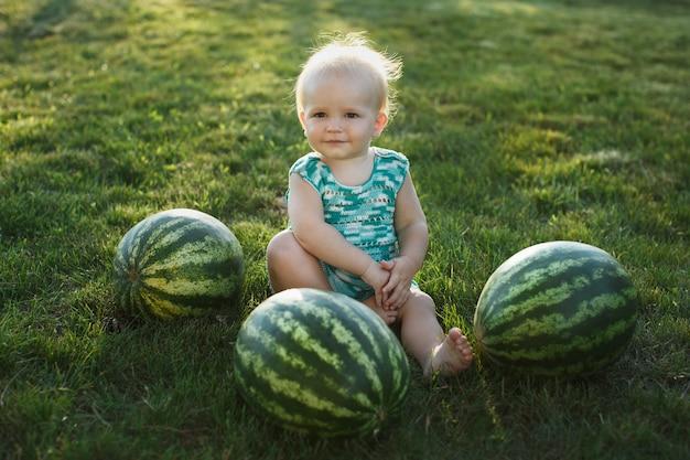 Mały chłopiec z arbuzem siedzący na trawie
