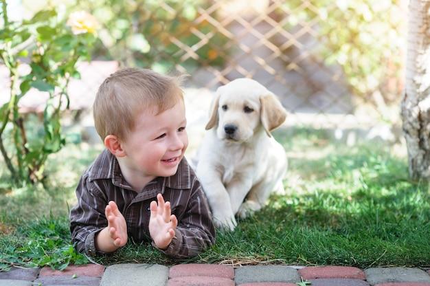 Mały chłopiec z białym szczeniakiem labradora leży na trawie latem