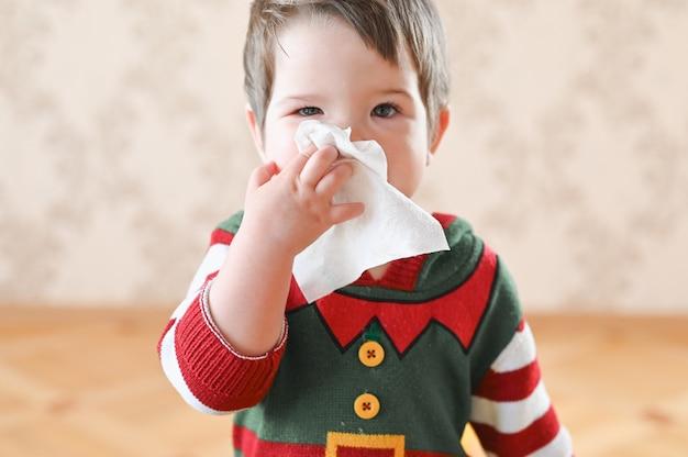 Mały chłopiec z ciemnymi włosami za pomocą chusteczki do czyszczenia nosa z przeziębieniem lub alergii na pyłki.