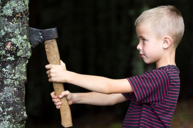 Mały chłopiec z ciężkim starym żelaznym ax ciie drzewnego atutu w lesie na letnim dniu. zajęcia na świeżym powietrzu i praca fizyczna.