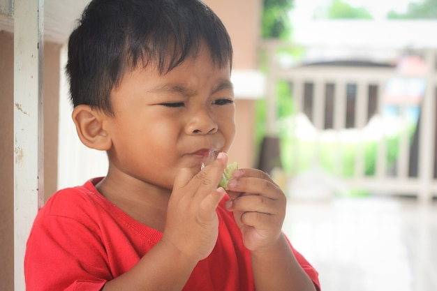 Mały chłopiec z cytrynami. kwaśny smak, negatywne emocje na twarzy,