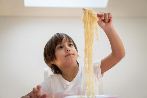 Mały chłopiec z długimi włosami jedzenie spaghetti