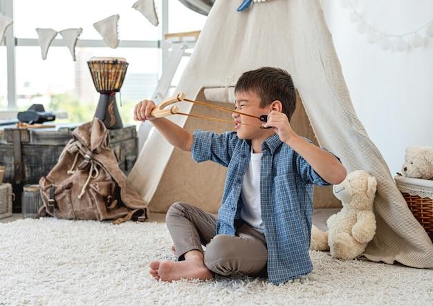 Mały chłopiec z drewnianą procą siedzi na podłodze w pokoju przed wigwamem