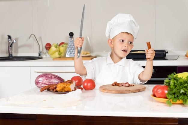 Mały chłopiec z dużym nożem w kuchni