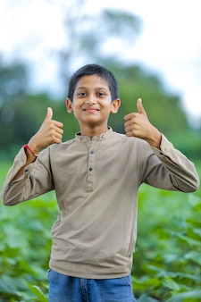 Mały chłopiec z indii / azji pokazujący kciuki do góry