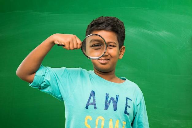 Mały chłopiec z indyjskiej szkoły azjatyckiej trzyma lupę stojącą na białym tle nad zielonym tłem tablicy