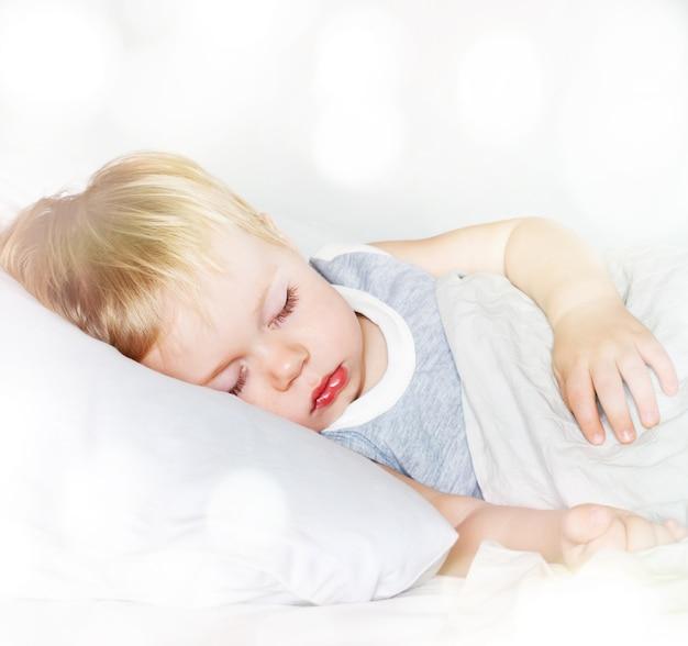 Mały chłopiec z jasnymi włosami. spanie