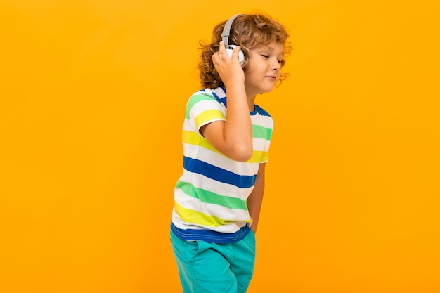 Mały chłopiec z kręconymi włosami w kolorowej koszulce i szortach słucha muzyki za pomocą dużych słuchawek na żółtym tle