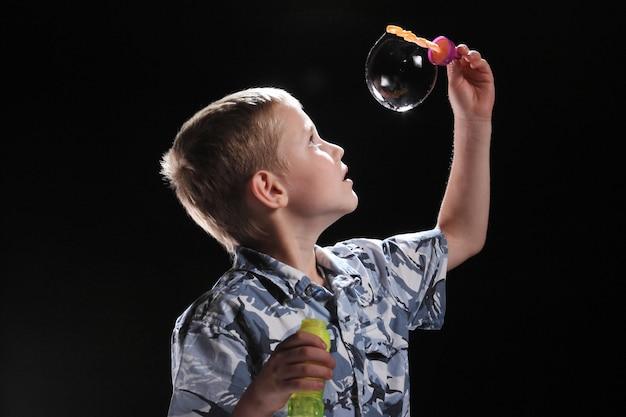 Mały chłopiec z kulką mydlaną