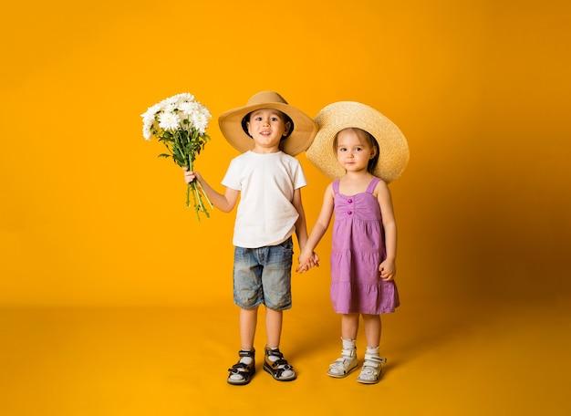 Mały chłopiec z kwiatami i dziewczyna w słomkowym kapeluszu stoją i trzymają się za ręce na żółtej powierzchni z miejscem na tekst