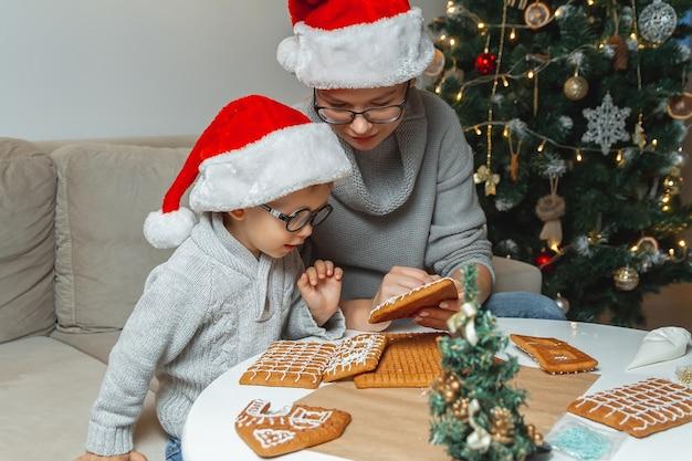 Mały chłopiec z mamą wspólnie dekorują świąteczny domek z piernika