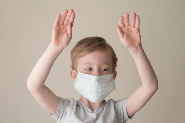 Mały chłopiec z maską i uniesionymi rękoma