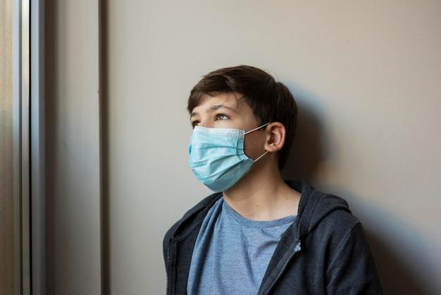 Mały chłopiec z maską medyczną, odwracając wzrok