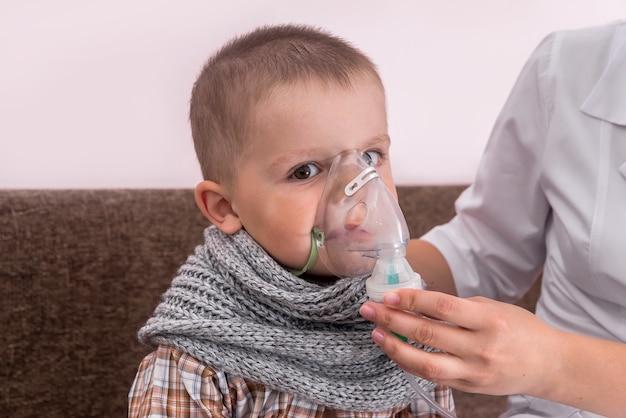 Mały chłopiec z maską nebulizatora na twarzy