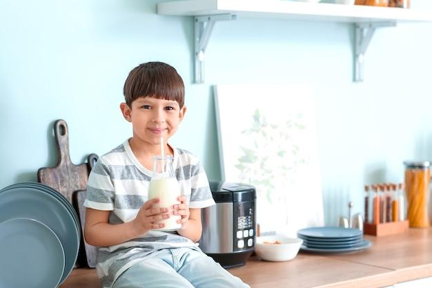 Mały chłopiec z mlekiem w kuchni