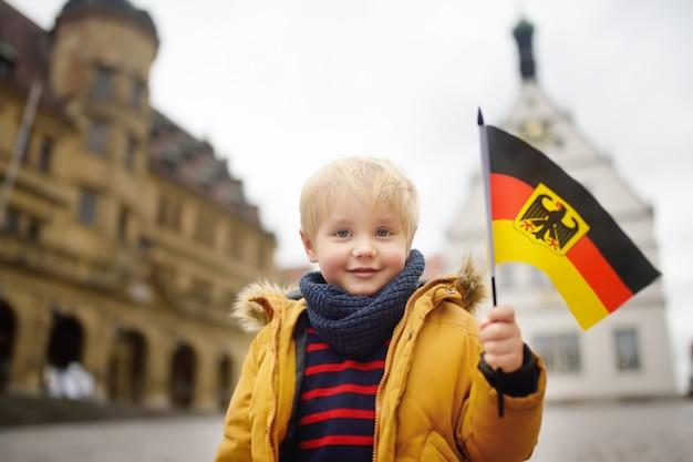 Mały chłopiec z niemiecką flagą na placu w rothenburg ob der tauber. małe miasteczko deutschland.