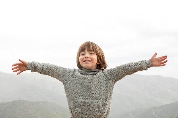 Mały chłopiec z otwartymi ramionami